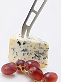 Piece of blue cheese with cheese knife and red grapes
