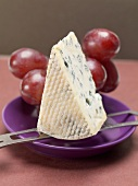 Piece of blue cheese on cheese knife, red grapes behind