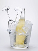 Bottle of sparkling wine & two empty wine glasses in ice bucket