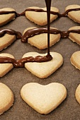 Decorating heart-shaped biscuits with couverture chocolate