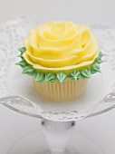 Yellow rose muffin on glass cake stand