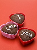 Heart-shaped chocolate muffins for lovers on red background