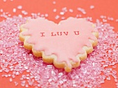 Heart-shaped biscuit on pink sugar