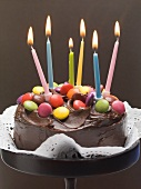 Chocolate cake with coloured chocolate beans and candles