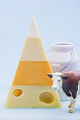Pyramid of hard cheeses, toy cow, milk can