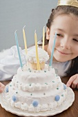 Little girl dressed as princess with birthday cake