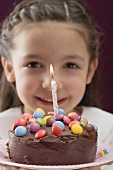 Little girl holding birthday cake with chocolate beans & candle