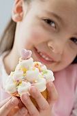 Little girl holding cupcake with cream and sugar confetti