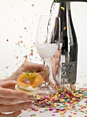 Hands holding cracker with smoked salmon & glass of Prosecco