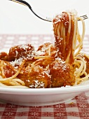 Spaghetti with tomato sauce and cheese on a fork