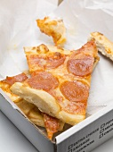 Several slices of pizza in a cardboard box