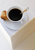Cup of black coffee with pastry in saucer