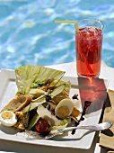 Salade niçoise and fruit juice by swimming pool