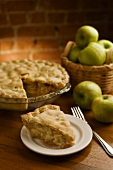 Stück Applepie vor angeschnittenem Kuchen, frische Äpfel