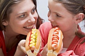 Woman and girl laughing and eating hot dogs