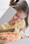 Girl looking at fresh pizza in pizza box