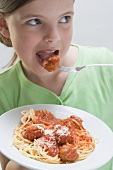 Girl eating spaghetti with meatballs
