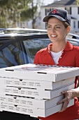 Smiling woman delivering five boxes of fresh pizza