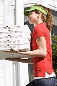 Woman in sun visor delivering five boxes of warm pizza