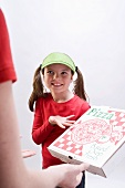 Girl in green sun visor showing pizza box