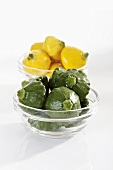 Green and yellow patty pan squashes in glass bowls