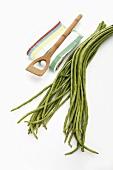 Yardlong beans, tea towel and wooden spoon