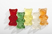 Five different coloured gummi bears in a row