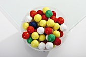 Coloured bubble gum balls in a bowl (overhead view)