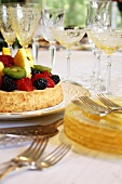 Fruit Tart on Table with Stacked Plates and Stem Glasses
