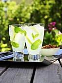 Two glasses of lemonade with fresh mint on table out of doors