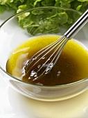 Salatsauce (Vinaigrette) in Glasschüssel mit Schneebesen