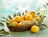 Lemons with leaves in a wooden dish