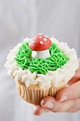 Hand hält Cupcake mit Marzipan-Fliegenpilz