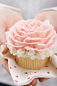 Hands holding cupcake with marzipan rose