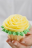 Hand holding cupcake with yellow marzipan rose
