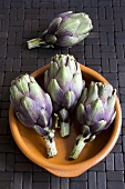 Four baby artichokes with terracotta dish