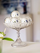 Christmas table decoration (silver baubles on glass stand)
