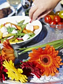 Gerberas and vegetable salad on a table (close-up)