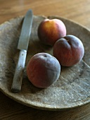 Three peaches with knife on a wooden plate