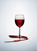 A glass of red wine with spilt wine