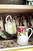 Cups and a jug on a shelf