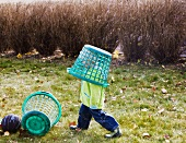 Little boy with a basket on his head in autumnal garden