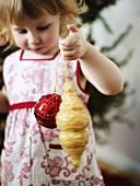 Little girl with Christmas tree ornaments