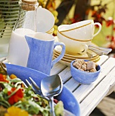 Salad, sugar, milk jug, cups & saucers on table out of doors