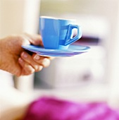 Hand holding a blue coffee cup and saucer