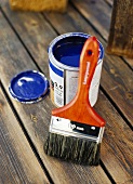 Pot of blue paint and paintbrush on a wooden floor