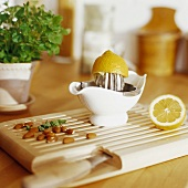 Lemon squeezer with lemon and almonds on a chopping board