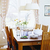 Dining table with plates and glasses by window