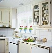 Einbauküche mit hellen Holzmöbeln, einem Sprossenfenster und Geranientöpfen auf dem Fensterbrett