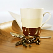 A coffee mug, spoon and coffee beans